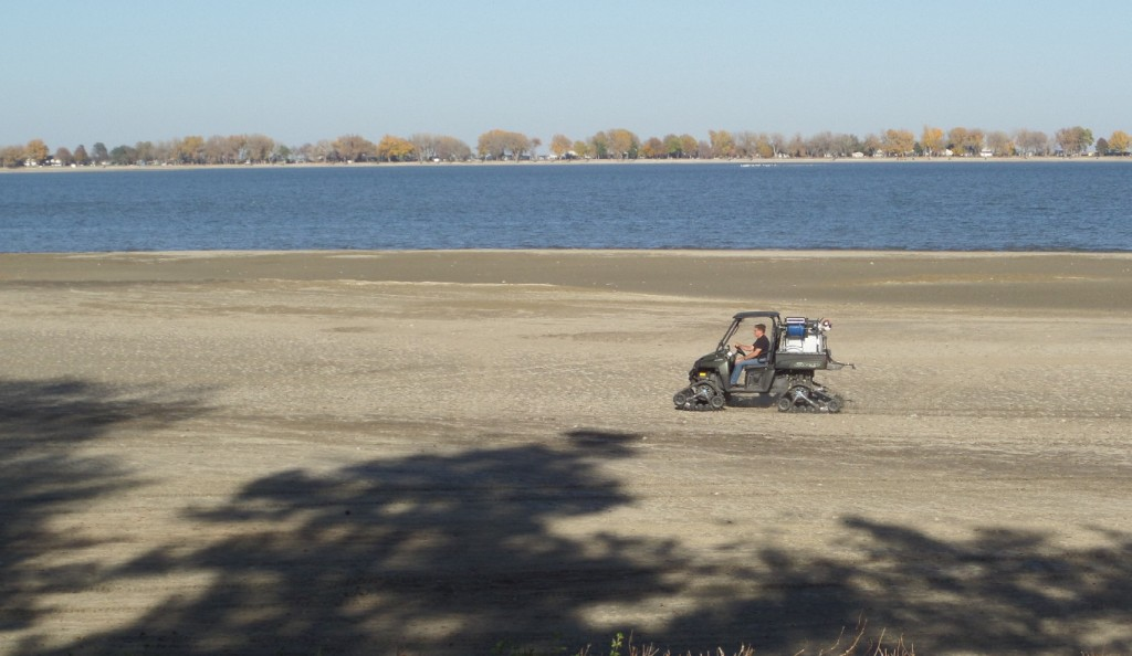 Kent Aden uses his personal utility vehicle to spray an aquatic herbicide on the shoreline at Johnson Lake.